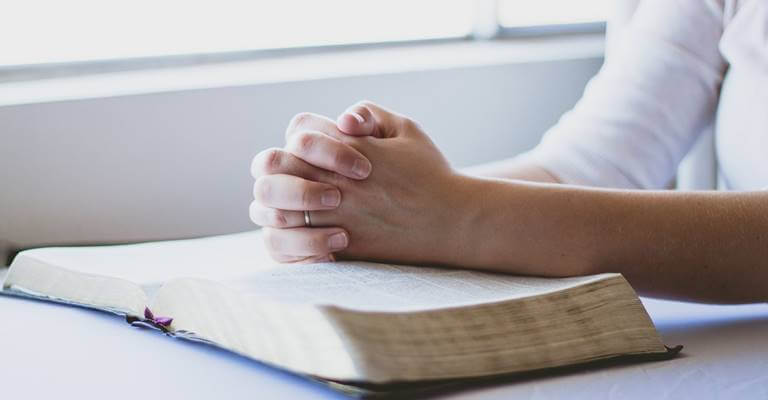 A prayer holding hands above the Bible